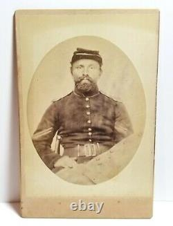 Union Army soldier holding Civil War Confederate coat, New York, cabinet photo